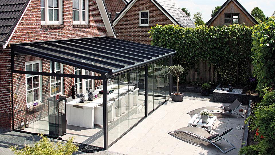 Terrassenüberdachung mit Ganzglas Schiebetüren im Garten